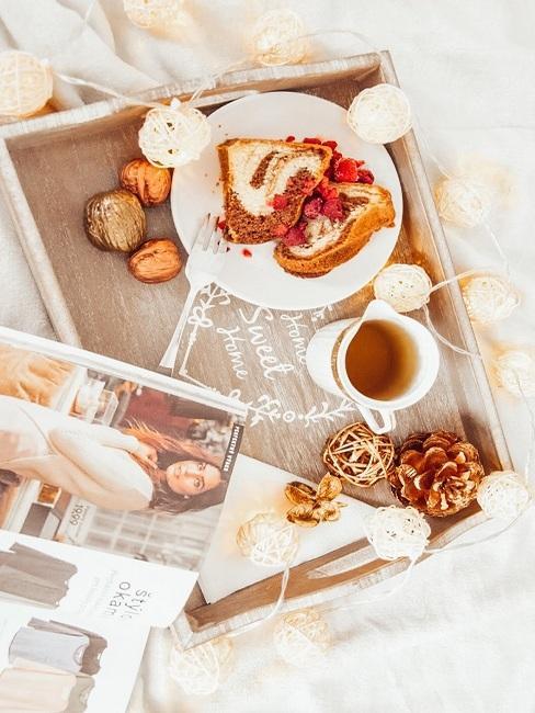 Drevený servírovací podnos na posteli, na ktorom je servírovaná bábovka, čaj a prírodné dekorácie s krásnym osvetlením v podobe girlandy