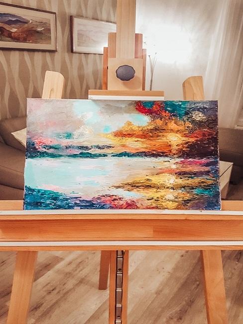 Farebný obraz na plátne stojaci na drevenom stojane