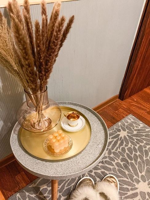 Malý sivý konferenčný stolík so zlatým tácom, na ktorom je zlatá šálka, sviečka a váza so sušenými trávami