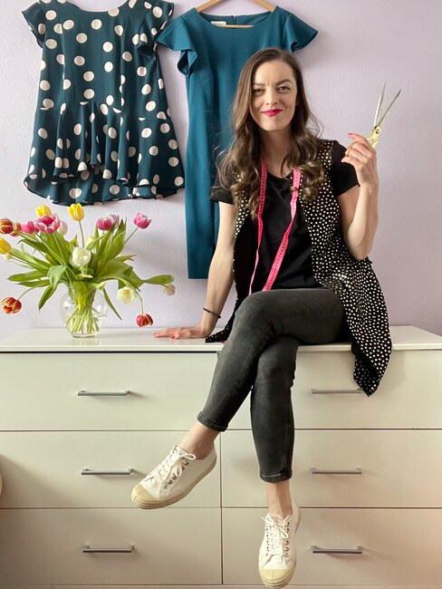 Ivanka, autorka blogu Mademoiselle Iva sediaca na bielej komode. V pozadí projekty šiat, na ktorých pracuje