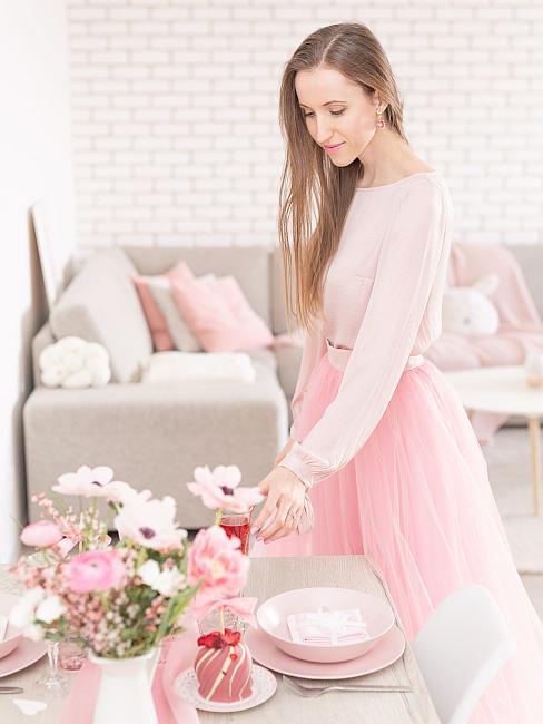 Obývačka spojená s jedálňou v ružových a bielych odtieňoch