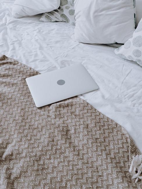 Posteľ s laptopom na vrchu
