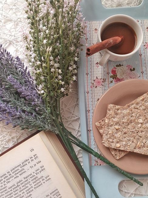 Umelé kvety naaranžované s kávou a knihou