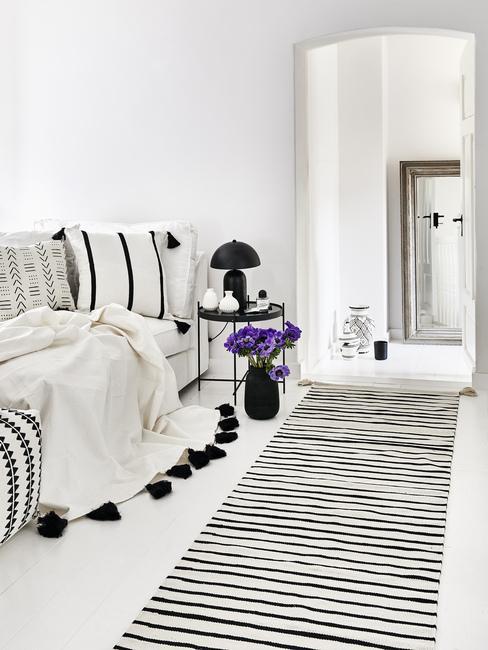 Fialové kvety a čierna podlahová lampa v spálni