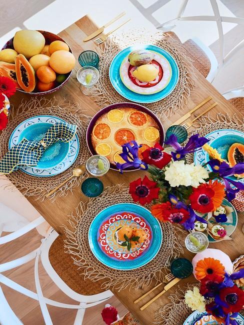 Taniere na stole v modrej farbe s ovocím a kvetinami