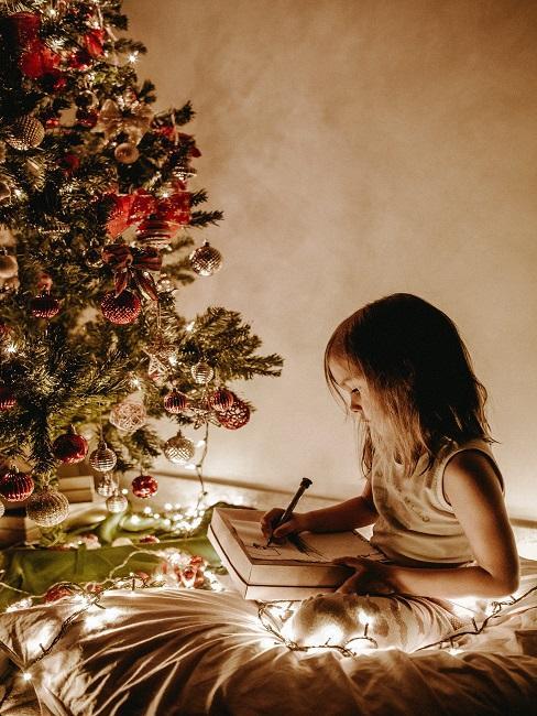Dieťa sa učí voanočné koledy pod stromčekom