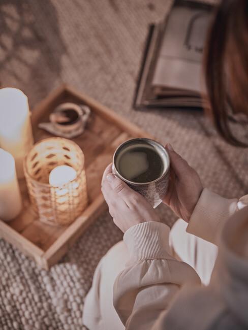 Dekoračný podnos so sviečkami a šálka čaju
