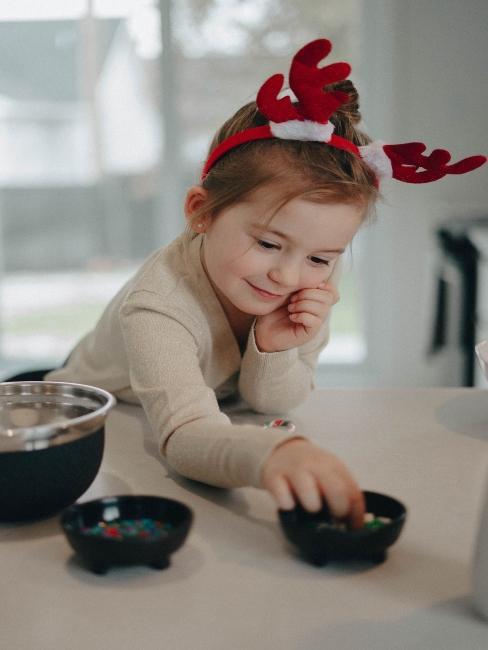 dievčatko pomáha pri tvorbe vianočných dekorácií