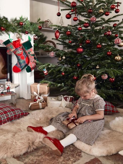 dievčatko s darčekmi pod vianočným stromčekom