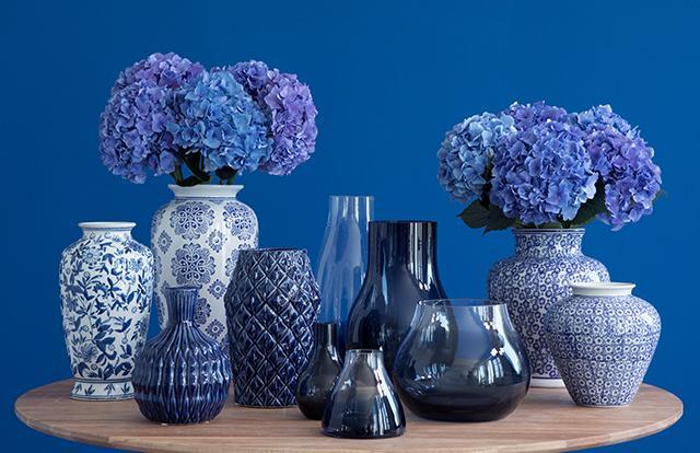 blauwe vazen met blauwe bloemen op een houten ronde tafel