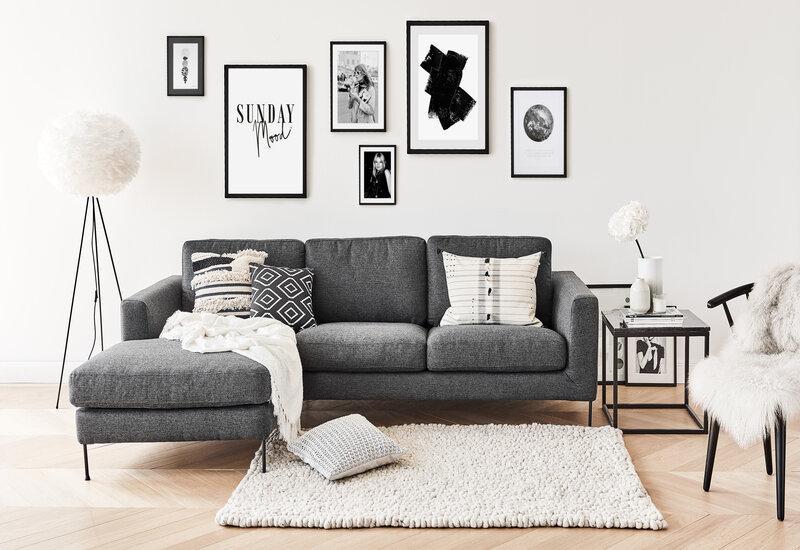 hoekbank grijs in een woonkamer met schilderijen