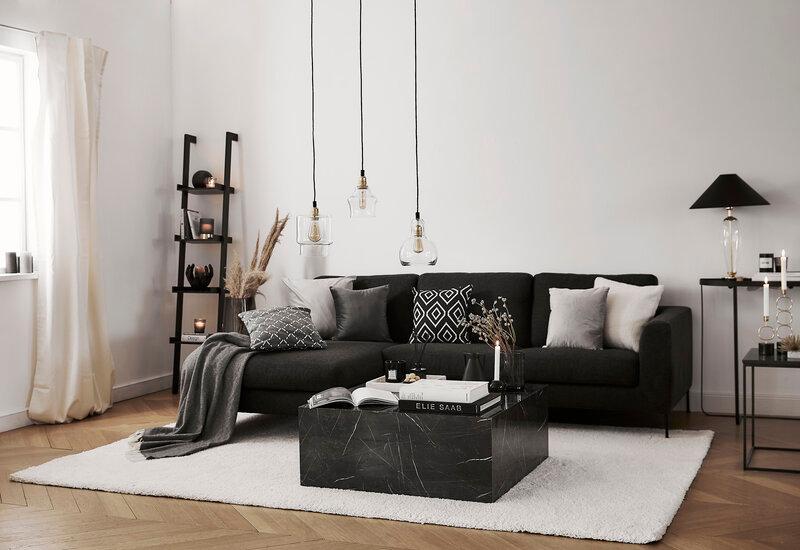 hoekbank zwart op een grijs vloerkleed