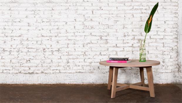 Ronde robuuste houten landelijke salontafel voor een witte betonnen muur
