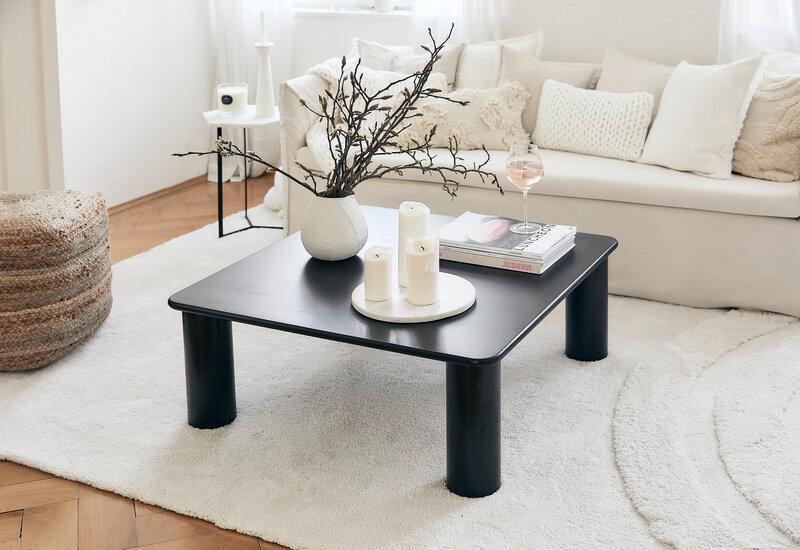 Zwarte vierkante salontafel met dikke ronde poten