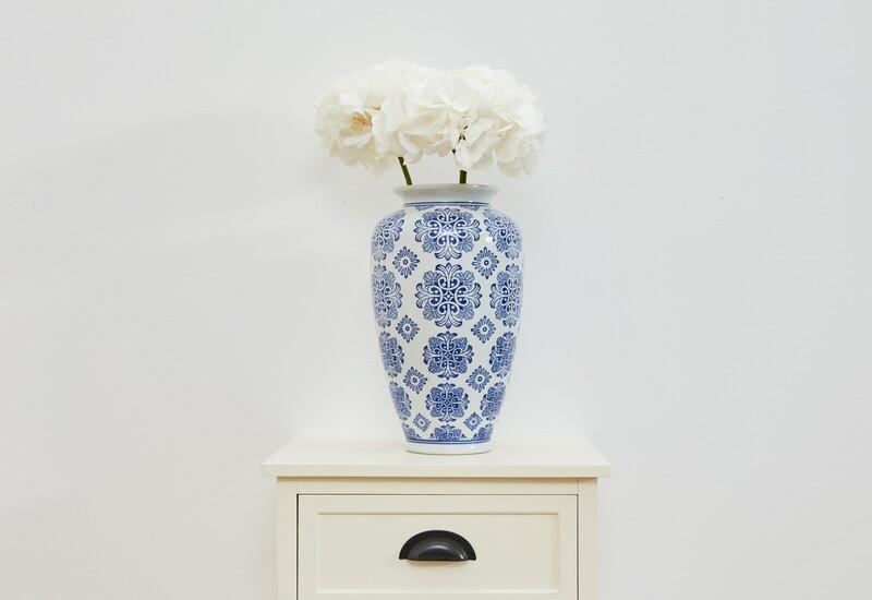 witte kast met een wit met blauwe bloemenvaas en witte bloemen