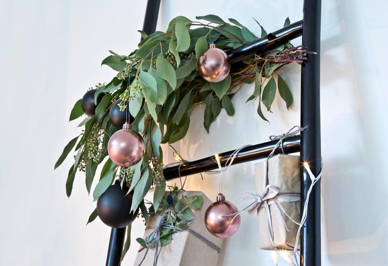 Onbreekbare kerstballen aan een zwarte decoratieve trap