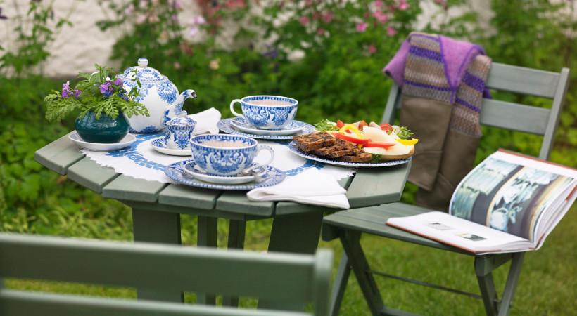 drewniany stół ogrodowy, na którym stoi rustykalna biało-niebieska zastawa