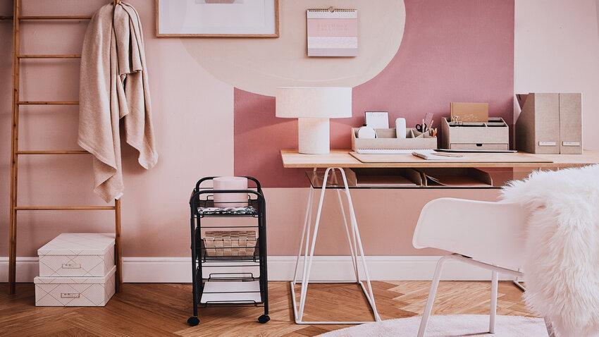 Drevený písací stôl v ružovo sfarbenej izbe