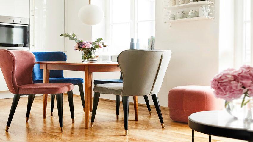 Okrúhly jedálenský stôl s farebnými stoličkami