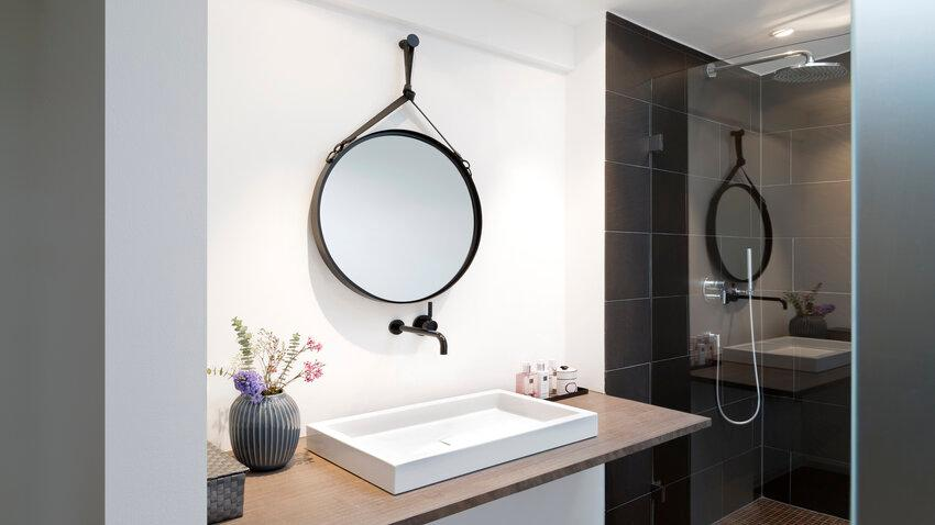 čierne závesné zrkadlo v kúpelni
