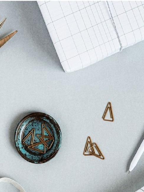 Ein Schreibtisch mit Block, kleinem Schälchen, Büroklammern in Dreieck-Form und einem Stift