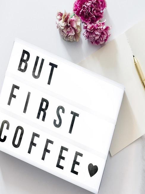 """Lightbox """"But first coffee"""" auf weißem Untergrund neben Blüten und einer Karte mit Stift"""