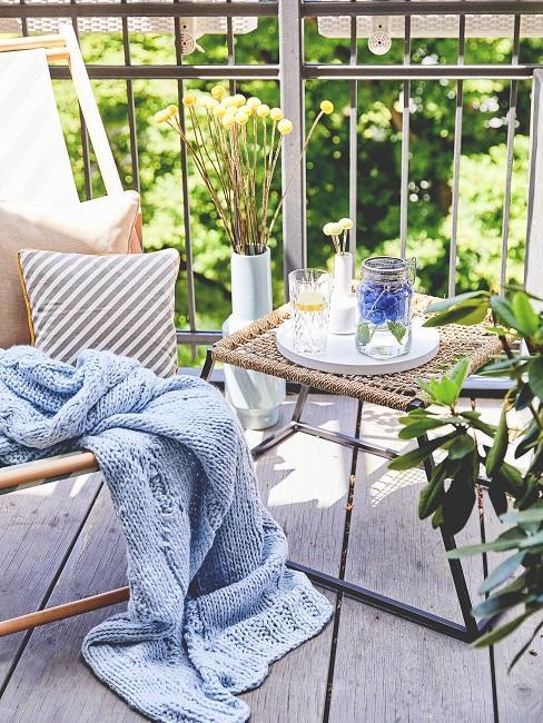 Balkon mit Tisch und einem Stuhl, darauf Kissen und eine Decke, Pflanzen als Deko