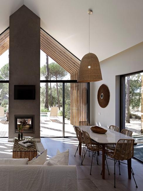 Wohnraum in einem Hotel mit viel Glasfläche, ein Sofa in Weiß, ein heller Tisch und Stühle plus Lampe in Rattan-Optik sind die Keypieces