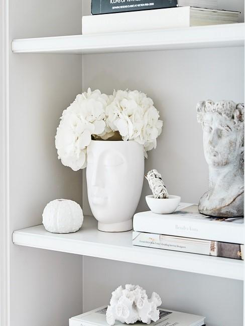 Weiße Vase mit Gesicht und weißen Blumen in Regal