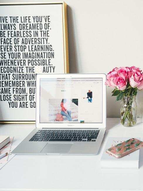 Schreibtisch mit Laptop, Blumen und einem Wandbild im Rahmen, einfach nur angelehnt an die Wand