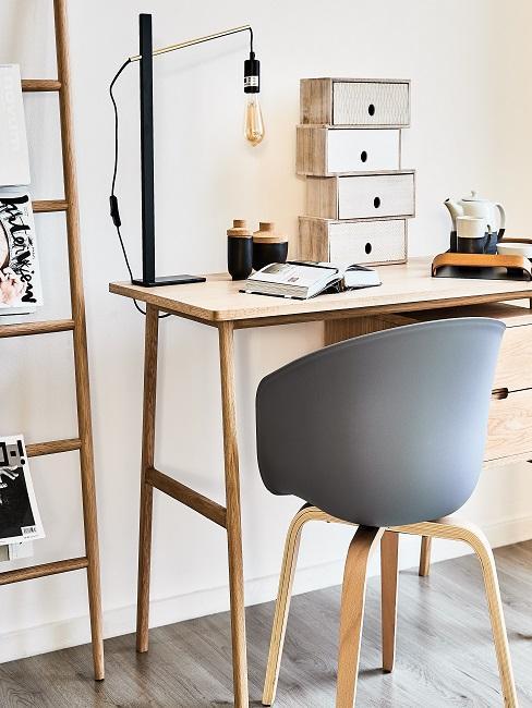 Kleiner Holz-Schreibtisch mit Lampe, kleinen Aufbewahrungsboxen und einem Buch, daneben eine Leiter mit zeitschriften als platzsparende Deko