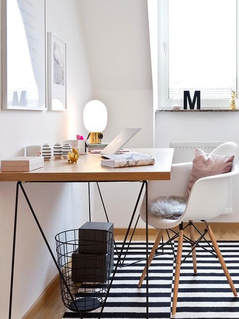 Holz-Schreibtisch mit weißem Stuhl auf einem schwarz-weiß gestreiften Teppich, Beleuchtung und Deko sorgen für eine angenehme Atmoshäre
