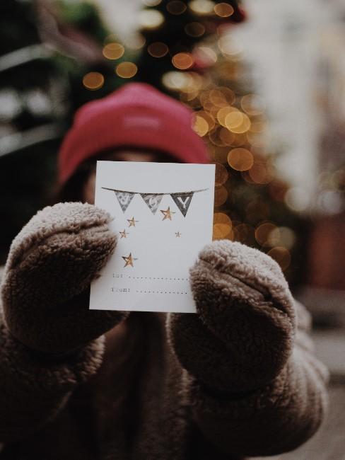 Ein Mädchen mit Mütze und Hanschuhen hält vor ihrem Gesicht eine selbstgebastelte Weihnachtskarte in die Kamera, im Hintergrund ein Weihnachtsbaum