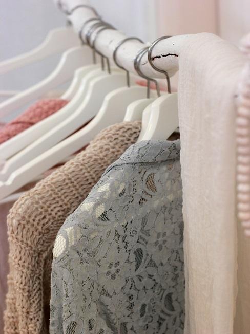 Ast dekorieren als Kleiderstange mit Kleiderbügeln und Klamotten