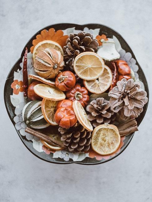 Holzschale dekorieren Herbst mit getrockneten Früchten und Tannenzapfen