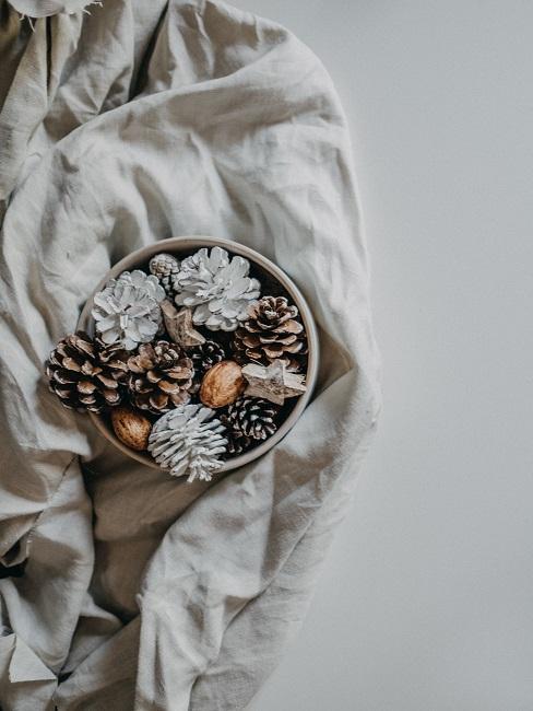 Herbstschale dekorieren Winter mit Tannenzapfel und Kugeln auf weißer Decke