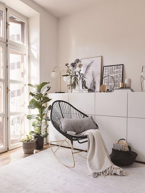Schwarzer Acapulco Chair im Zimmer dekoriert mit Kissen und Decke neben Kommode und Pflanze