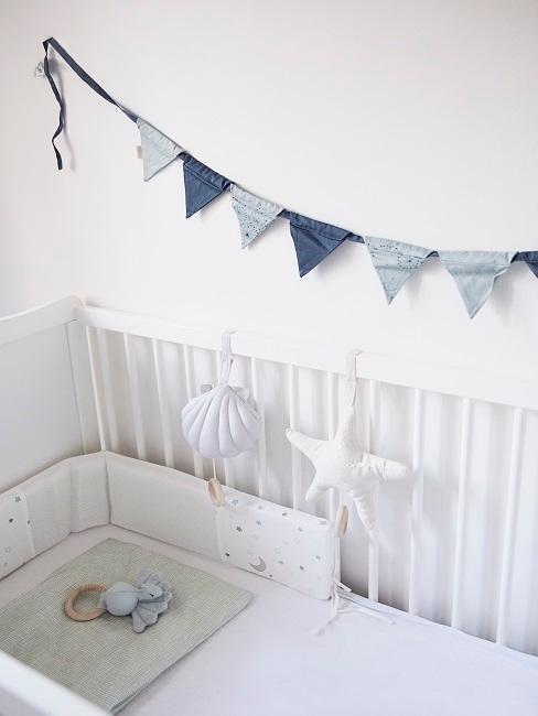 Babyzimmer Wandgestaltung mit einer Wimpelkette in Blau, die über dem weißen Babybettchen angebracht ist.