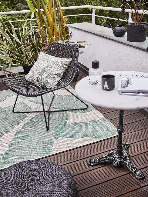 Rattanstuhl mit Kissen auf Teppich neben Beistelltisch auf Balkon