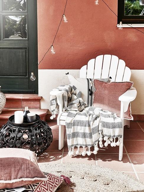 Balkon Sessel aus Holz mit Kissen, Decke und Lichterkette neben Beistelltisch