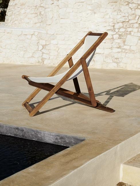 Liegestuhl auf Terrasse neben Pool