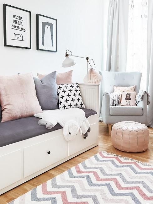 Scandi Kinderzimmer mit Sofabett, Kissen, Sessel und buntem Teppich