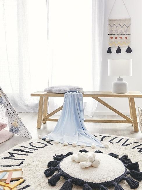 Sitzbank mit Plaid und Tischleuchte auf rundem Teppich