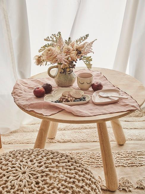 Kleiner Holztisch auf Teppich mit Essen und Blumen