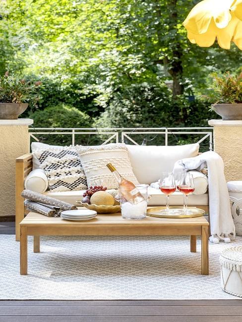 Sitzbank mit Kissen, Decke und Couchtisch auf schmalen Balkon