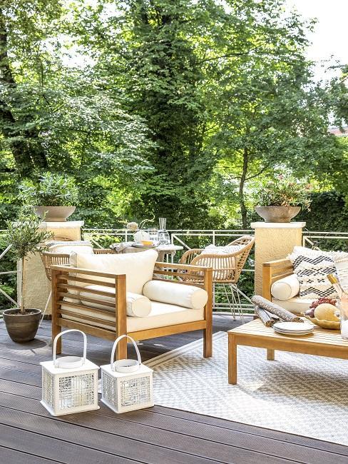 Terrasse mit Loungesessel, Couchtisch, Laternen und Teppich