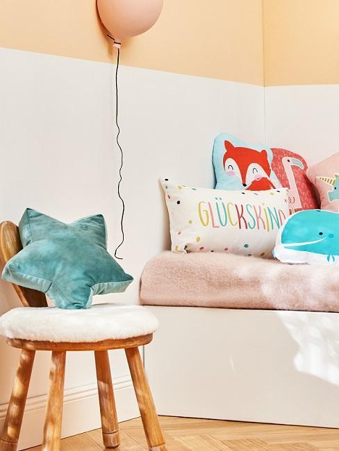 Apricotfarbene Wand im Kinderzimmer mit bunten Kissen auf dem Bett