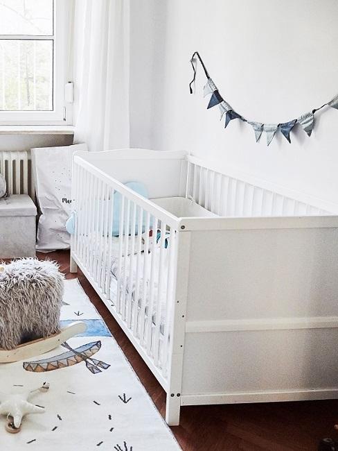 Wimpelkette über Babybett als Wanddeko im Babyzimmer