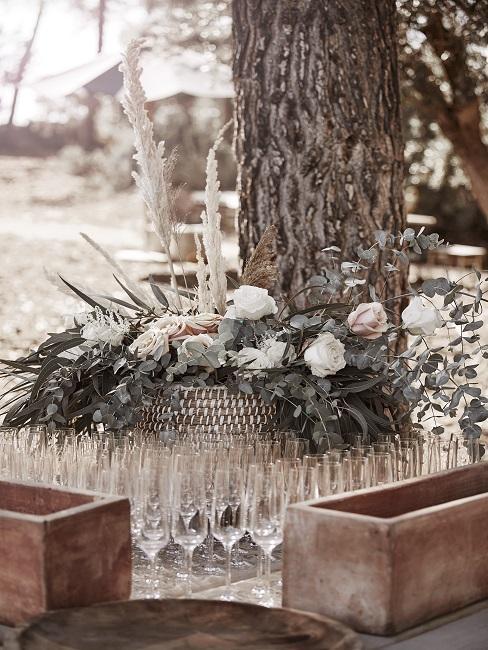 Blumenarrangements neben Sektgläsern