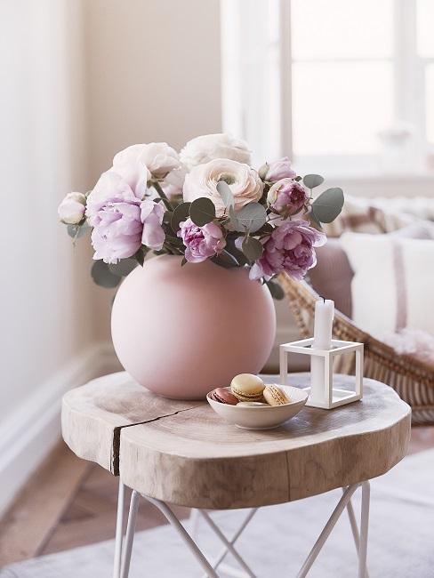 Blumenarrangement in rosafarbenr Kugelvase auf Holzhocker